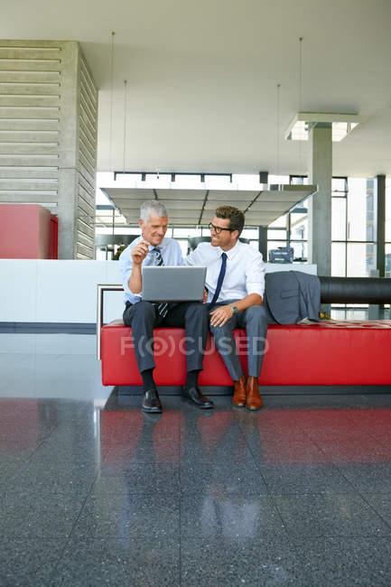 Два усміхнений підприємців, які працюють на ноутбуці в офісі лобі — стокове фото