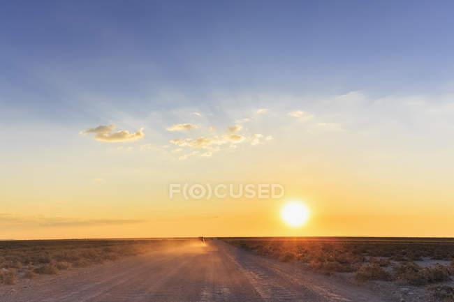 Véhicule tout-terrain circulant sur route de gravier au coucher du soleil, parc national d'Etosha, Namibie — Photo de stock