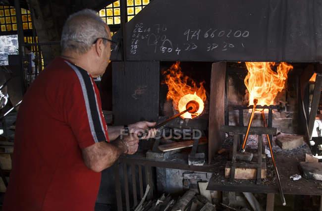 Человек, использующий печь на стекольном заводе на Майорке — стоковое фото
