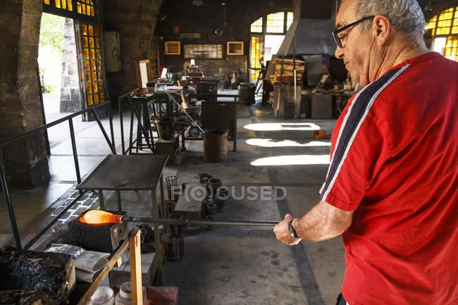 Человек, работающий с расплавленным стеклом на фабрике на Майорке — стоковое фото