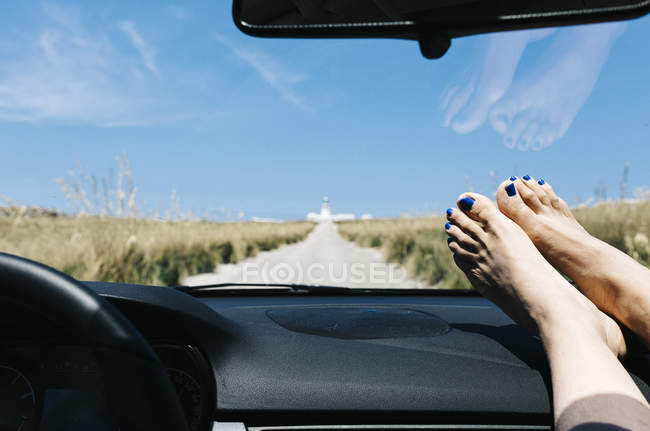 Spain, Menorca, feet on the dashboard, driving on empty road on vacations with a lighthouse in the background — Stock Photo