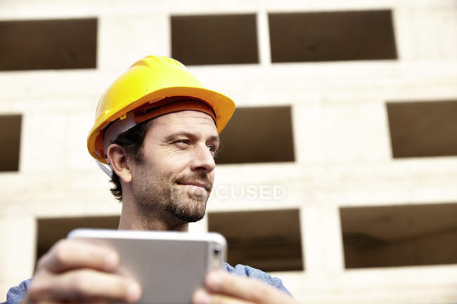 Man with hard hat on construction site holding cell phone — Stock Photo