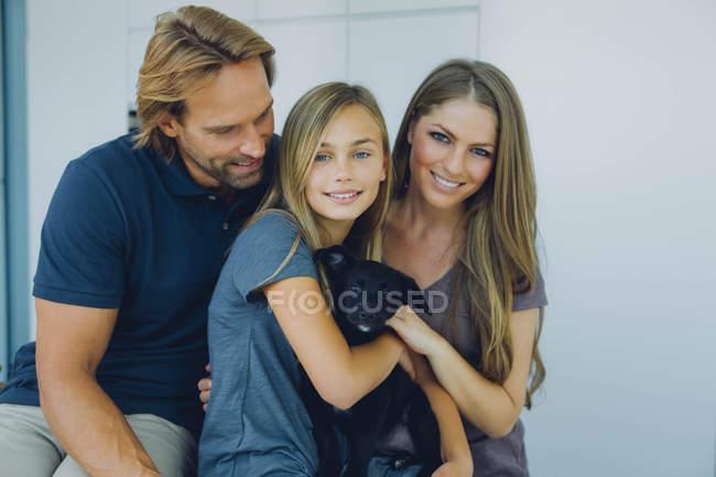 Retrato de pai sorridente, mãe e filha com cachorro — Fotografia de Stock