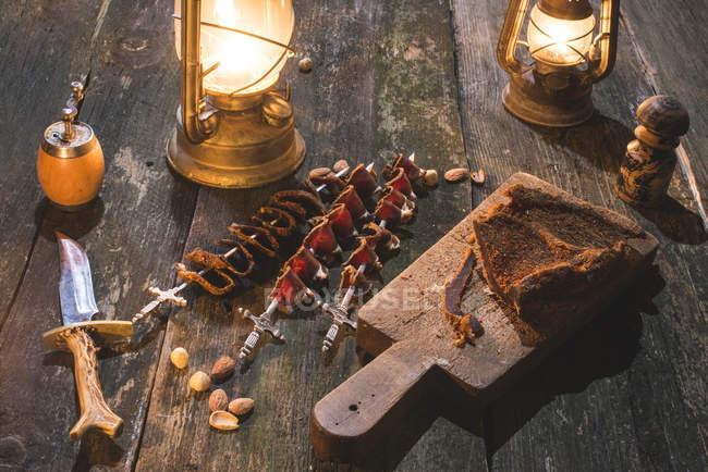 Trockenfleisch auf Holztisch mit Laternen — Stockfoto