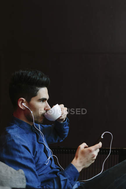 Profile of young man hearing music with earphones while drinking coffee in front of black background — Stock Photo