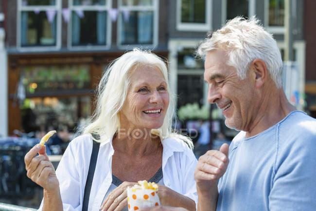 Нидерланды, Амстердам, счастливая пожилая пара ест картошку фри — стоковое фото