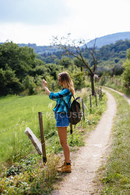 Alto Adige, teenage girl with backpack standing on a path taking a photo — Stock Photo