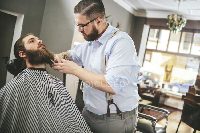 Barber cutting beard of a customer in barbershop — Stock Photo