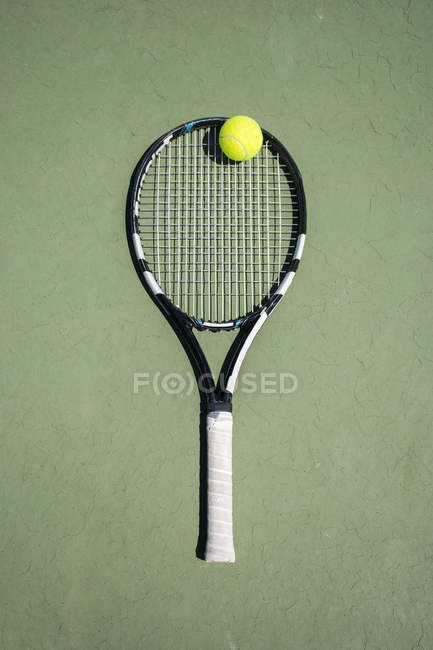 Raqueta y pelota en una cancha de tenis - foto de stock