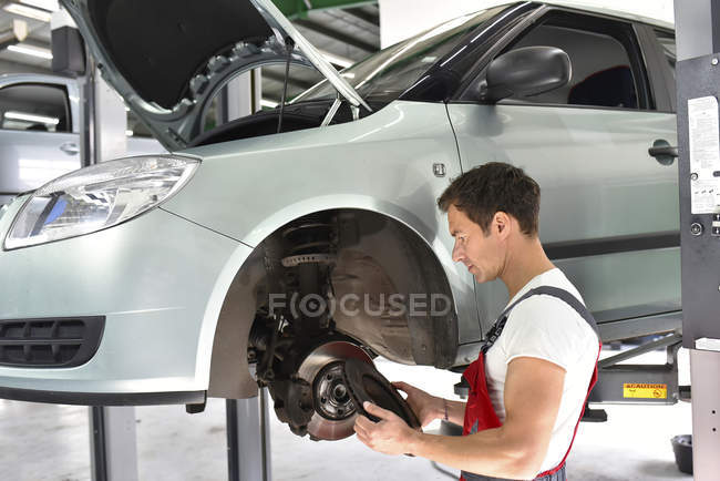Car mechanic working in repair garage, checking brake disc — Stock Photo