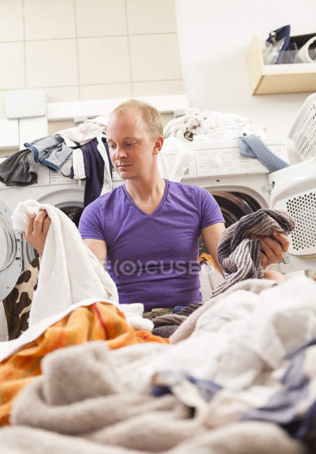 Jovem sentado entre roupa suja — Fotografia de Stock