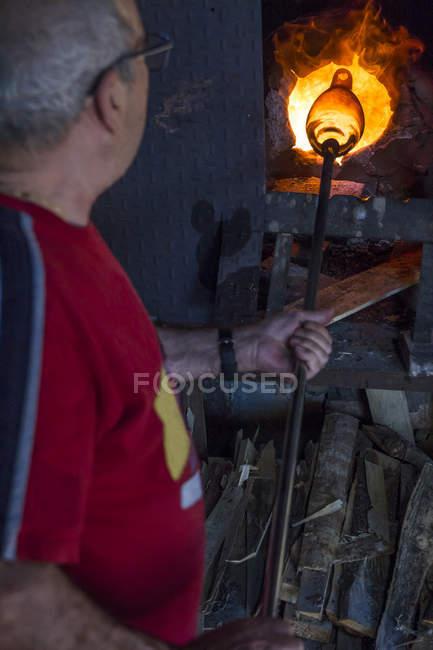 Homem usando um forno em uma fábrica de vidro — Fotografia de Stock