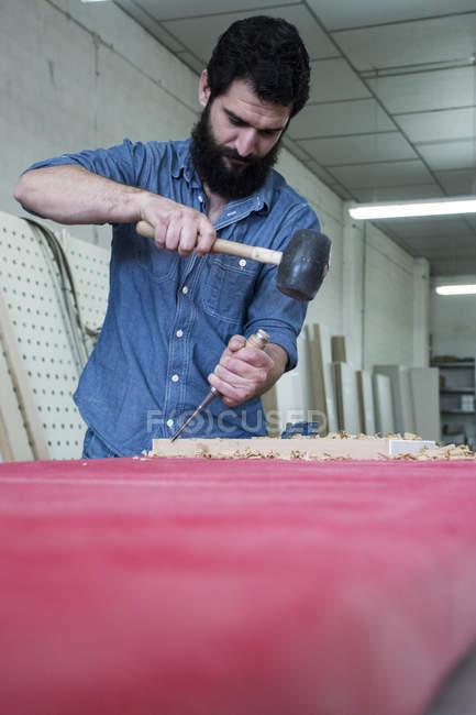 Карпентер, використовуючи зубилом і молотком — стокове фото
