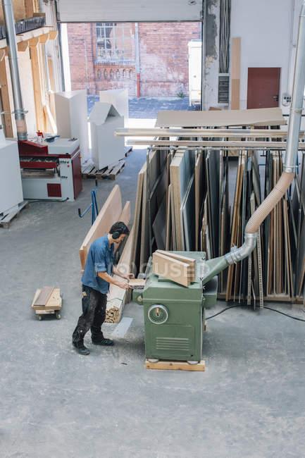 Carpenter working with planing machine — Stock Photo