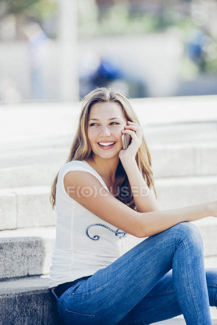 Portrait of smiling teenage girl telephoning with smartphone — Stock Photo