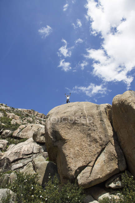 Climber on the top of a rock with outstretched arms — Stock Photo