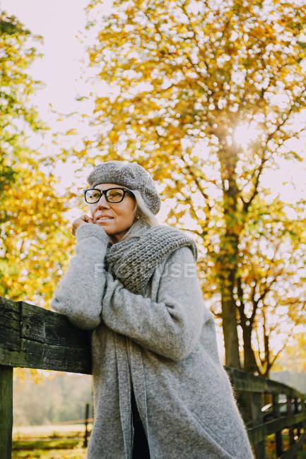 Retrato de mulher vestindo malhas cinza em um parque outonal — Fotografia de Stock