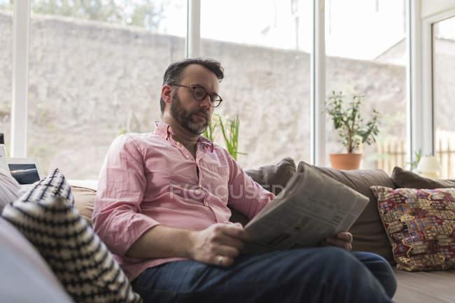 Älterer Mann sitzt auf Couch und liest Zeitung — Stockfoto