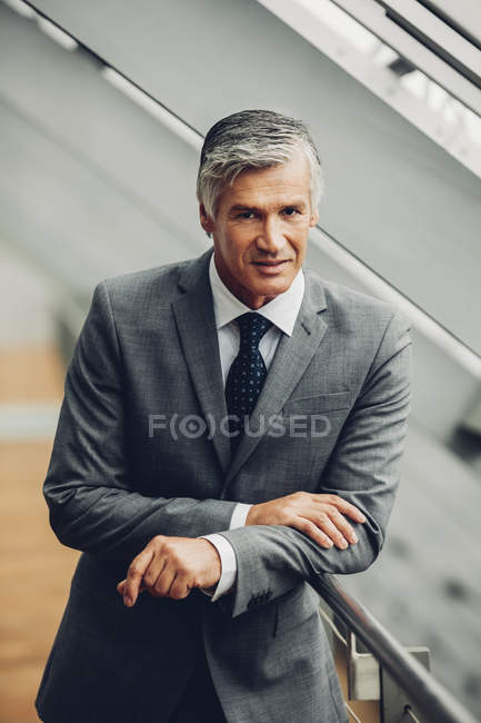 Mature businessman standing by railing — Stock Photo