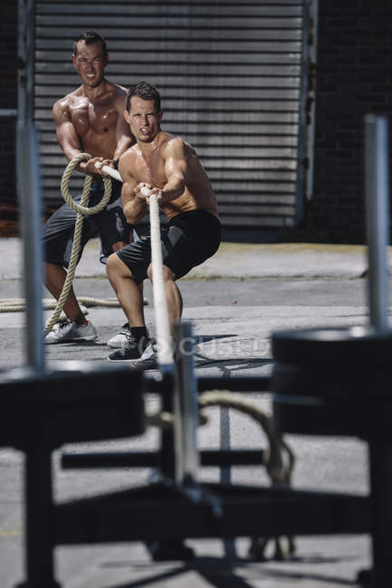 Two CrossFit athletes pulling rope together at gym — Stock Photo