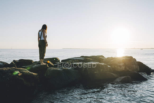 France, Pornichet, woman standing on rocks at seafront by sunset — Stock Photo