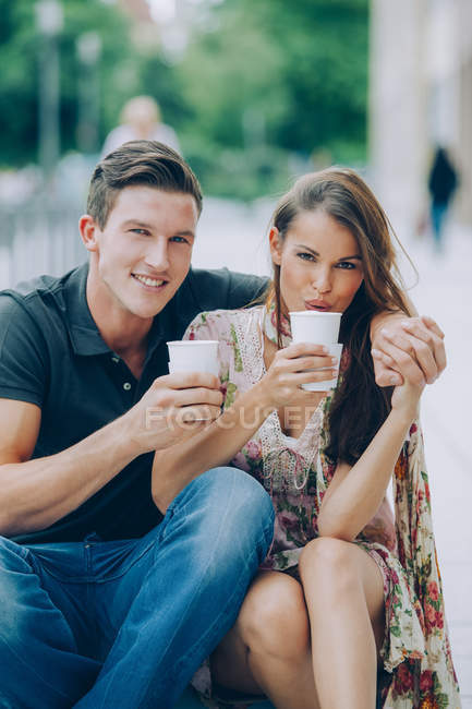 Smiling young couple drinking coffee outdoors — Stock Photo