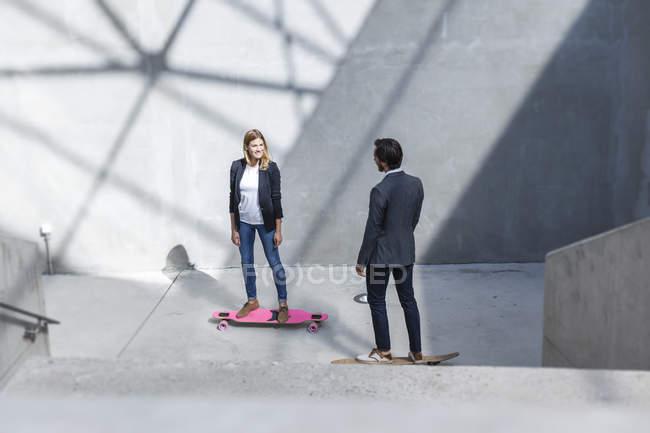 Два ділових людей, стоячи на скейтборд в сучасній архітектурі — стокове фото
