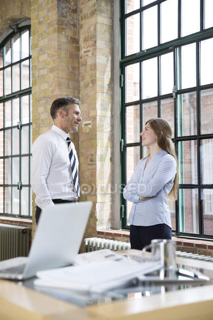 Mature man and woman talking in office — Stock Photo
