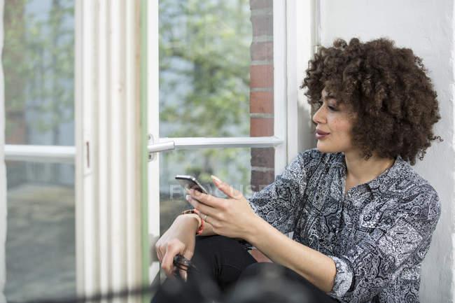 Donna con il telefono cellulare che osserva dalla finestra — Foto stock