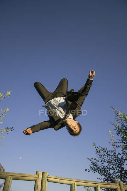 Low angle view of Businessman jumping backwards — Stock Photo