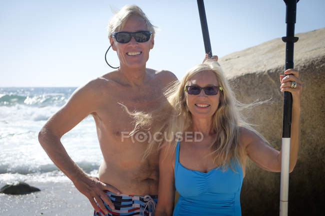 Portrait of happy senior couple holding paddles by the sea — Stock Photo