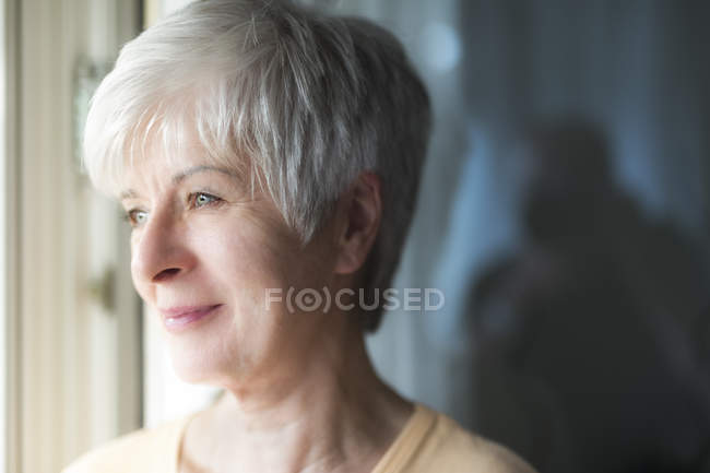 Portrait of smiling senior woman looking through window — Stock Photo