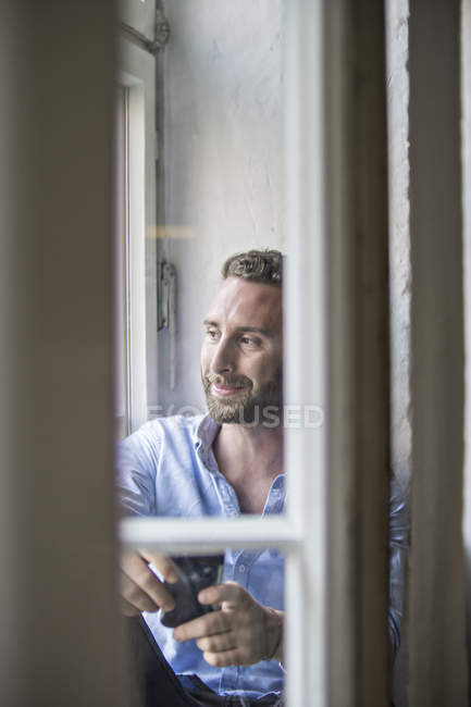 Smiling young man looking out of window — Stock Photo