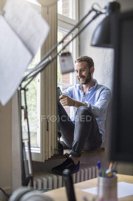 Smiling young man in office sitting at the window — Stock Photo