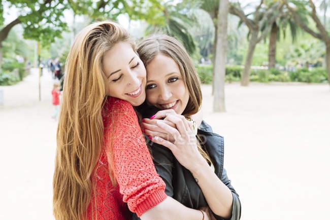 Due amiche che si abbracciano in un parco — Foto stock