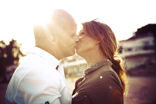 Kissing couple at backlight outdoors — Stock Photo