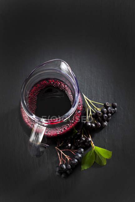 Sumo de Aronia em garrafa com amoras na ardósia — Fotografia de Stock