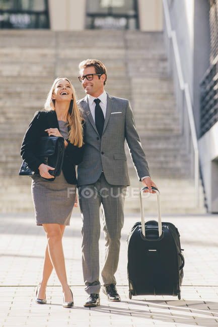 Happay businessman and businesswoman walking together with suitcase — Stock Photo