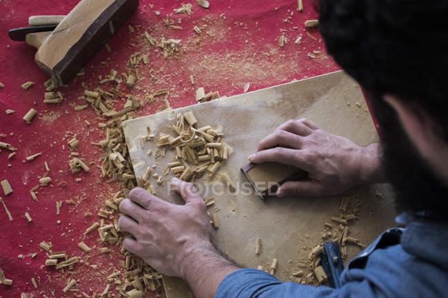 Hands of carpenter sanding a wood plank — Stock Photo