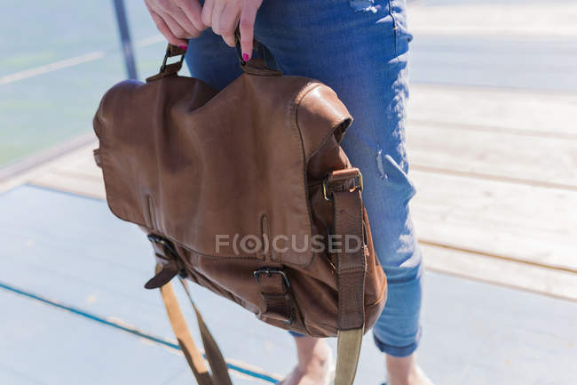 Woman holding old leather bag on jetty near sea — Stock Photo