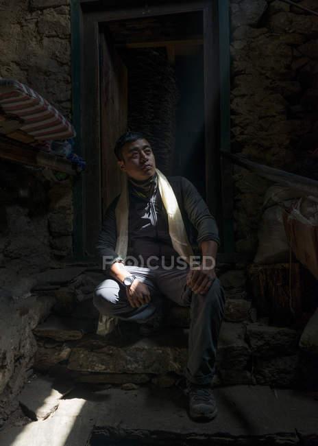 Ray of light falling on man sitting on stoop — Stock Photo
