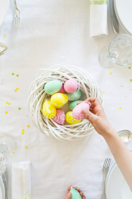 Little girl decorating dining table with Easter eggs — Stock Photo