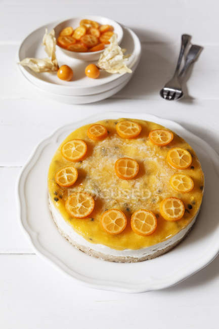 Mango passion fruit cake decorated with slices of kumquat — Stock Photo