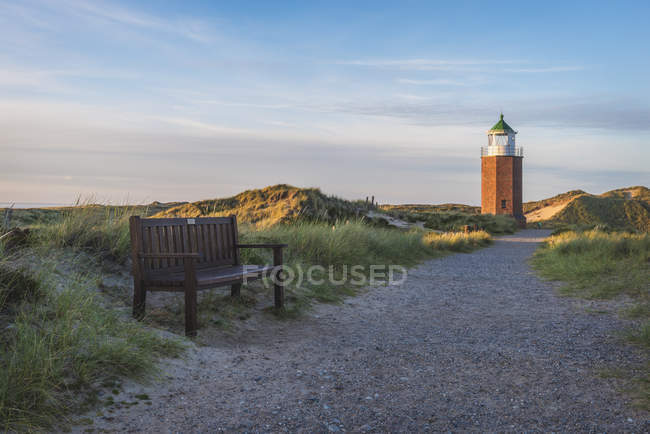 Wooden bench on footpath to lighthouse — Stock Photo