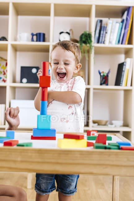 Portrait de petit garçon excité jouant avec des briques de construction — Photo de stock