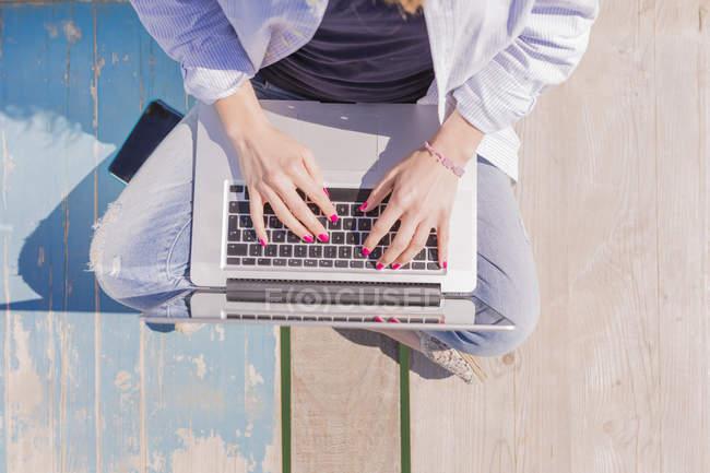 Молода жінка з ноутбуком, сидячи на пристані — стокове фото
