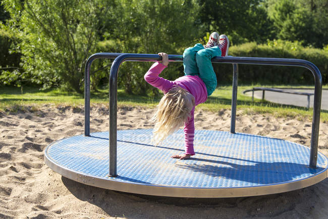 Petite fille jouant sur une aire de jeux — Photo de stock