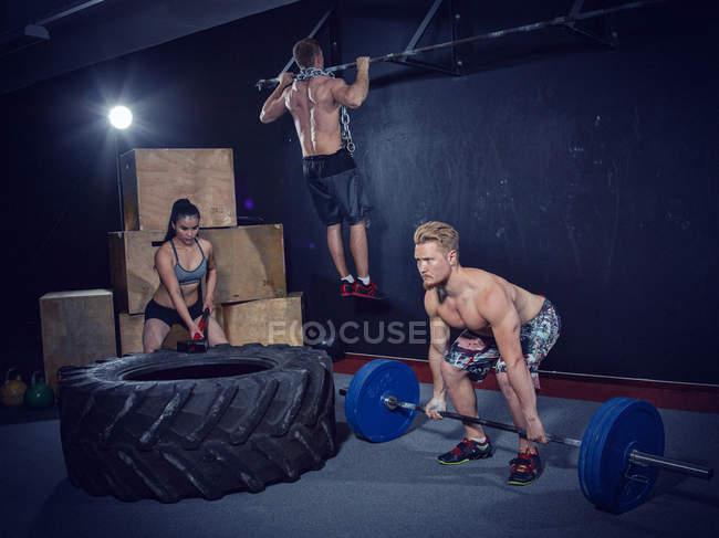 Три crossfit спортсменів, заняття в тренажерному залі разом — стокове фото