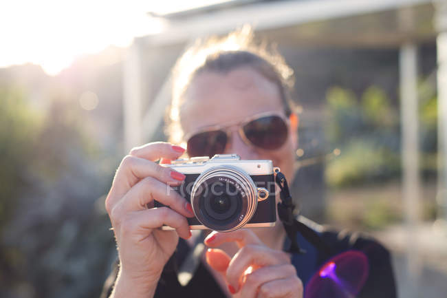 Woman holding camera outdoors — Stock Photo