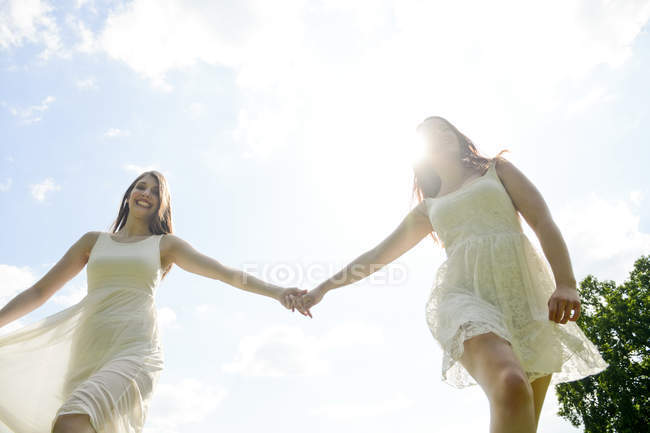 Two happy young women hand in hand — Stock Photo